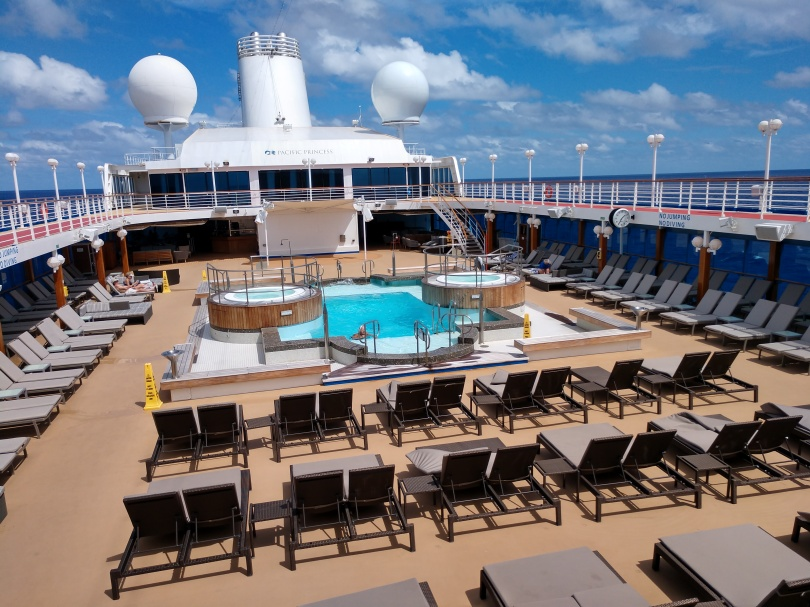 Photo of the pool area of the Pacific Princess cruise ship, taken in March 2020. A single man stands in the pool. It is surrounded on all sides by rows of mostly-empty lounge chairs. In the distance, you can just see a single couple at the far end.